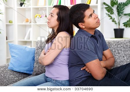 angry couple after  conflict, sitting on couch back to back