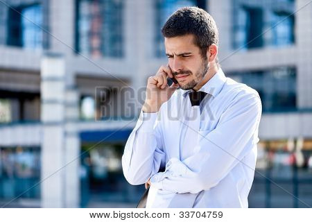 Businessman using a mobile phone standing outside a modern office building