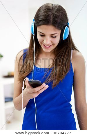 Beautiful teenager girl listening music over smart phone