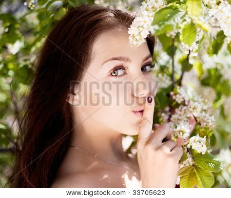 beautiful brunette woman saying hush be quiet, outdoors in the park on a warm summer day
