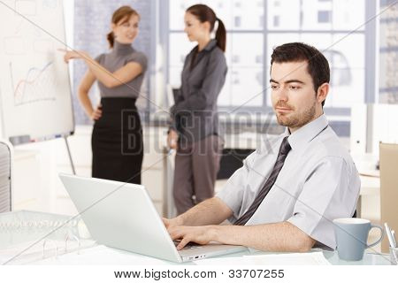 Young businessman sitting at desk, working on laptop, businesswomen standing by whiteboard, discussing diagrams in the background.