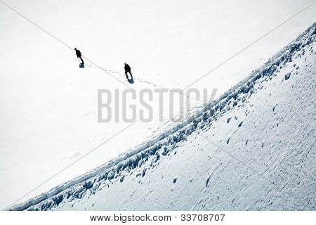Team of two alpinists climbing a glacier
