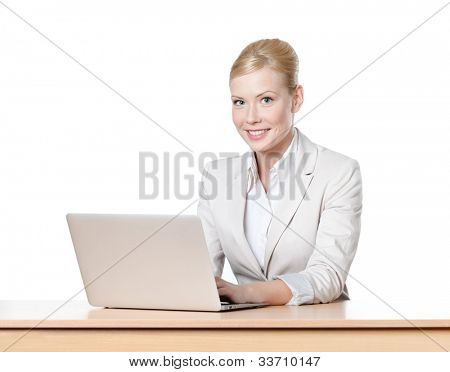 Young businesswoman sitting at a office table with laptop, looking at the camera