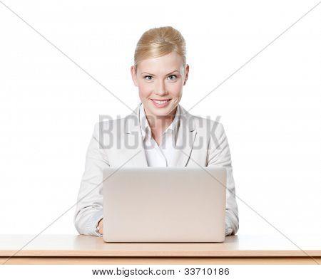 Young businesswoman sitting at a desk with laptop, looking at the camera