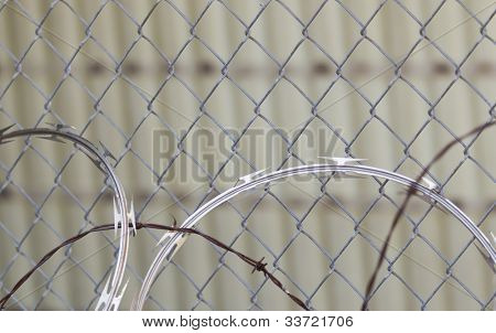 Closeup view of razor wire against a fence