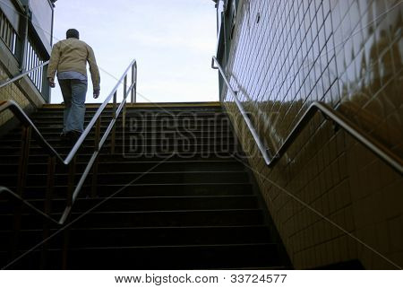 man walking up subway staircase