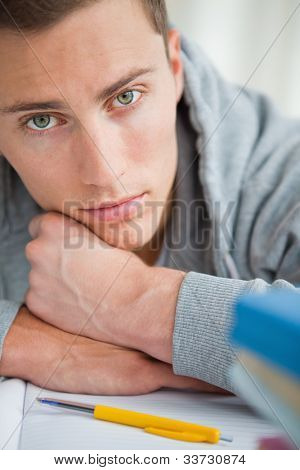 Portrait of a depressed student  on his desk with green eyes