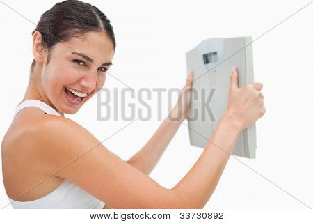 Cheerful young woman holding a scales against white background