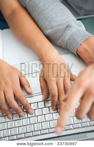 High view of students hands working with a laptop while typing and pointing the screen
