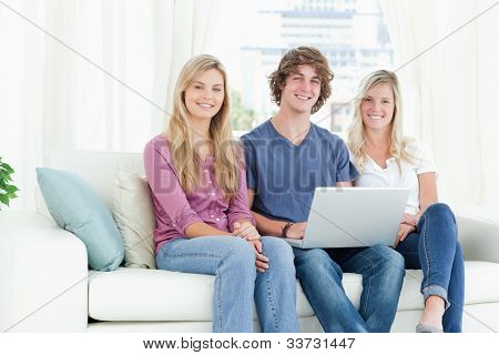 A smiling group of people sitting together as they use a laptop while looking at the camera