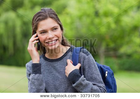Young smiling girl standing in a park while looking away and talking on the phone
