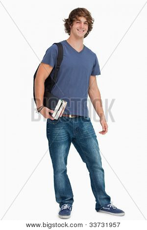 Portrait of a male student with a backpack holding books against white background