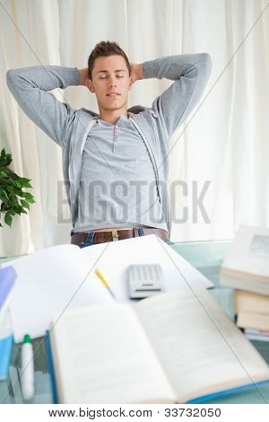 Student stretching with closed eyes in front of his homework