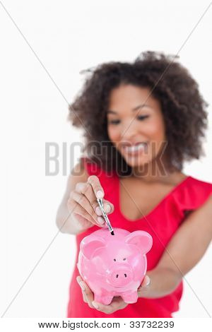 Pink piggy bank receiving bank notes against a white background
