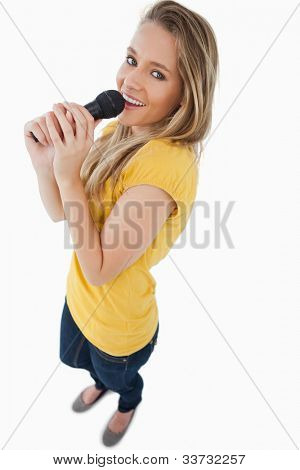 Fisheye view of a blonde girl singing with a microphone against white background