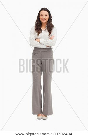 Pretty employee with folded arms against white background