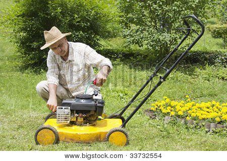 Mid age man repairing lawn mower