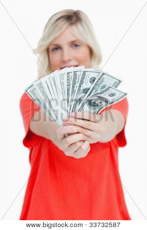 A fan of dollar notes held by a woman against a white background