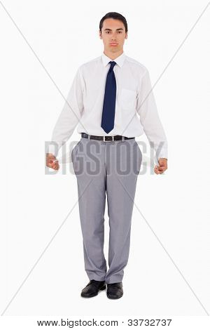 Upset man showing his empty pockets against white background