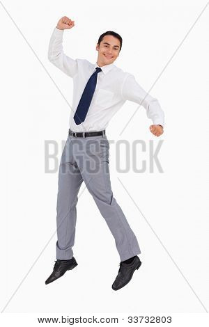 Businessman raising his arms and jumping against white background