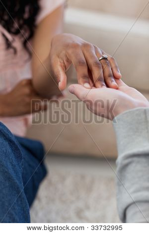 A hand with a wedding ring on it is placed in her friends hand while they sit down