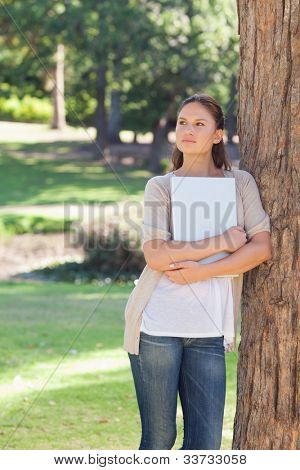 Young woman with a laptop leaning against a tree