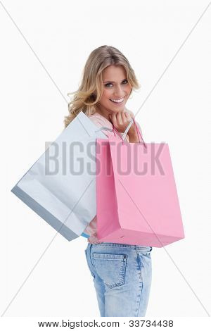 A woman looking back at the camera is carrying shopping bags over her shoulder against a white background
