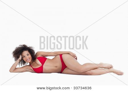 Smiling young brunette woman lying down while looking straight at the camera