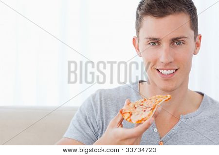A smiling man holding a slice of pizza in his hand