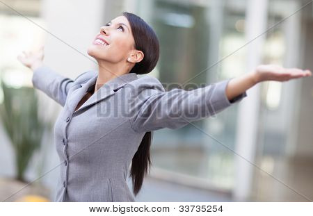 Successful business woman with arms open and looking up