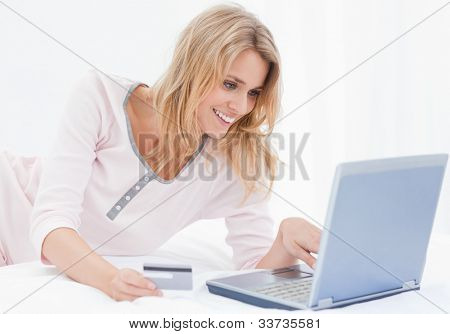 A smiling woman lying on her bed, using her laptop and credit card to order items online.
