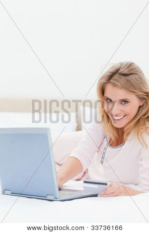 A smiling woman lying on her bed as she uses her laptop while looking straight ahead.