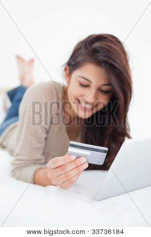 A close up focus shot on the credit card that the smiling woman is holding as she uses her tablet.