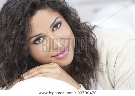 Studio portrait of a beautiful young Latina Hispanic woman smiling resting on her hands