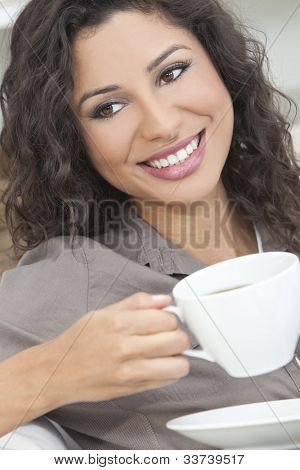 Beautiful young Latina Hispanic woman smiling, relaxing and drinking a cup of coffee or tea
