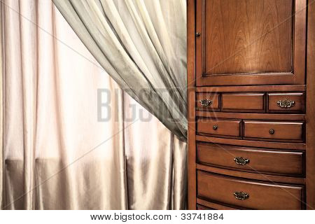 Details of elegant interior.  Chest of drawers and curtain.