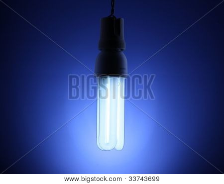A lit energy saving light bulb on blue background