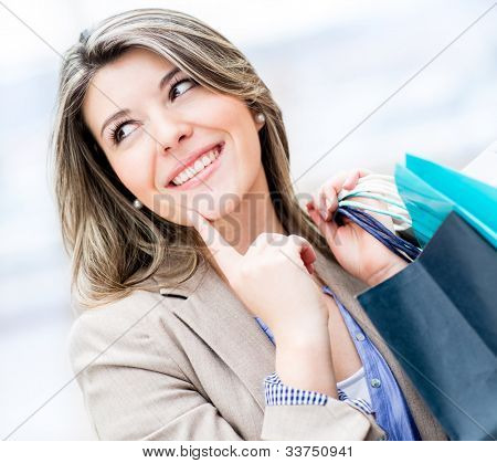 Thoughtful girl holding shopping bags and smiling