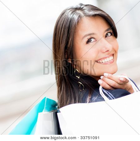 Pensive woman holding shopping bags and smiling