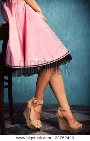 female legs in wedge high heel shoes and romantic pink skirt