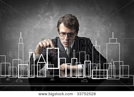 Young businessman putting a skyscraper in the project of a city