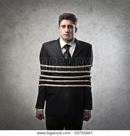 Young businessman tied with ropes