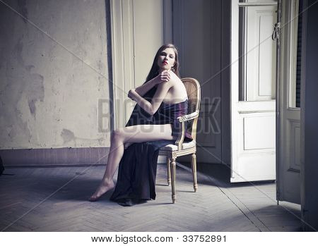 Beautiful elegant woman sitting on a chair in an empty room