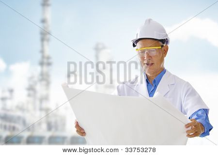 Senior Asian engineer with blueprints standing outside plant