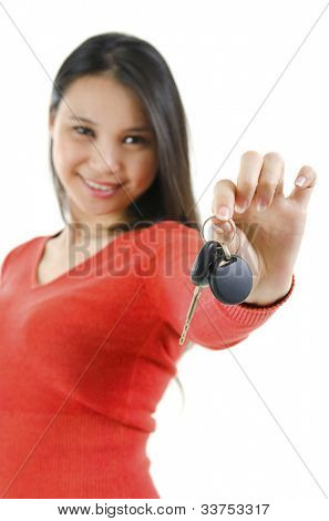 Happy Asian woman showing her new car key, isolated on white, focus on car key