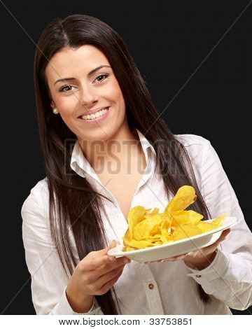 portrait of a young woman holding a potato chips plate over a black background
