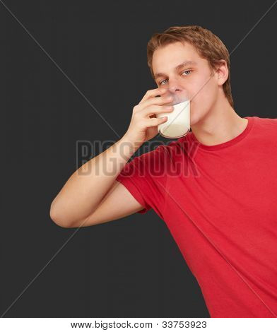 portrait of a young man drinking milk over a black background
