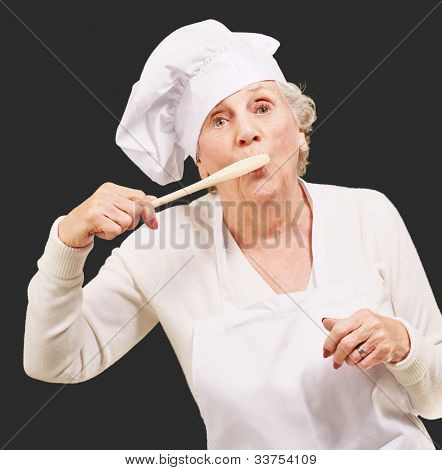 portrait of a cook senior woman with a wooden spoon on her mouth over a black background