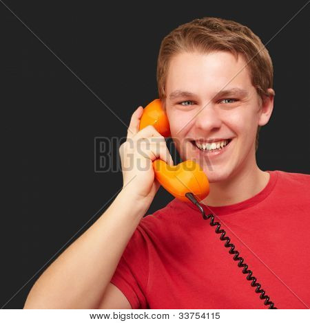 portrait of a young man talking with a vintage telephone over a black background