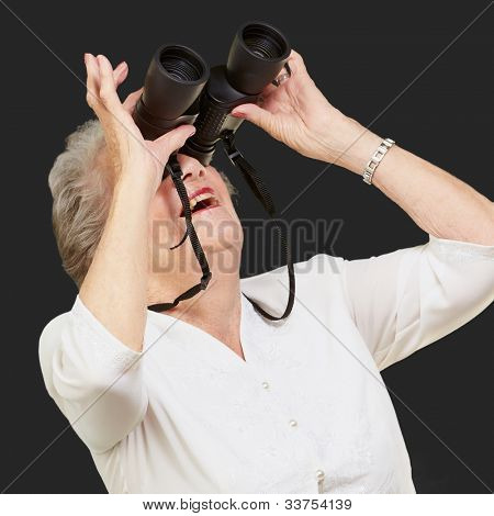 portrait of a senior woman looking through binoculars over a black background